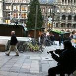 """Marienplatz, a praça da Maria. Originalmente chamada Schrannen, foi renomeada com o objetivo de pedir à Virgem Maria proteção à cidade contra a cólera. Em Marienplatz é possível ver o """"New town hall"""" e o """"Old town hall"""", ambos construídos em estilo gótico."""